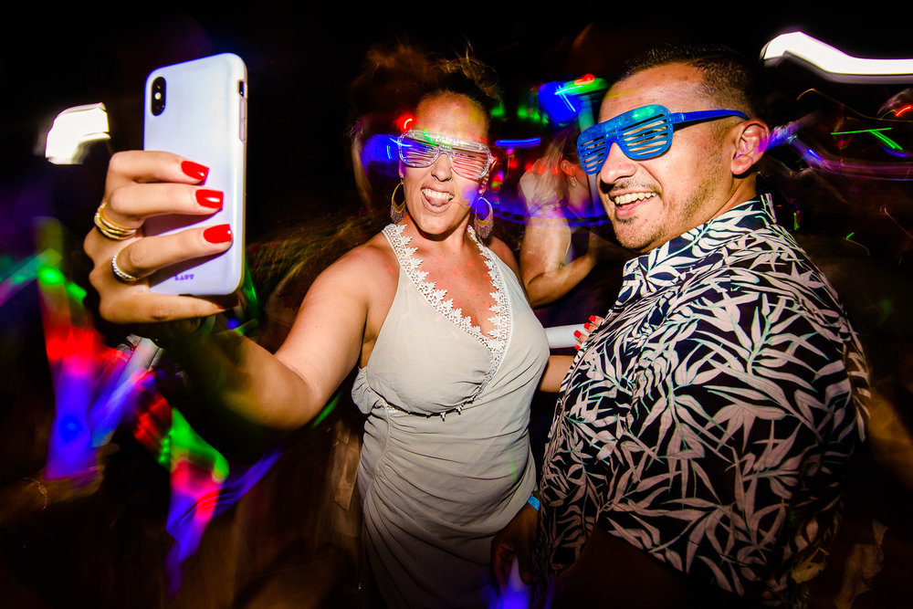 A beautiful couple selfie on the dance floor. Both wearing glasses made of glow bands and is dancing with full energy at the evening party of the lovely couple-destination wedding of the wonderful couple Chelsea and Jay at the beautiful Pueblo Bonito Sunset, Mexico. GVphotographer is an amazing destination wedding photographer based in Los Cabos, Mexico