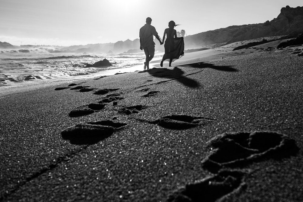 Young engaged couple walk along a desert beach in Baja, Mexico