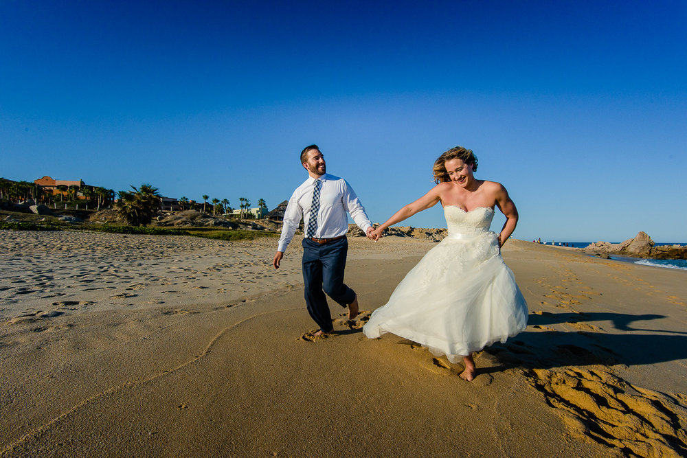 Bride and groom running on the beach during their one year photo anniversary at the Sheraton´s beach