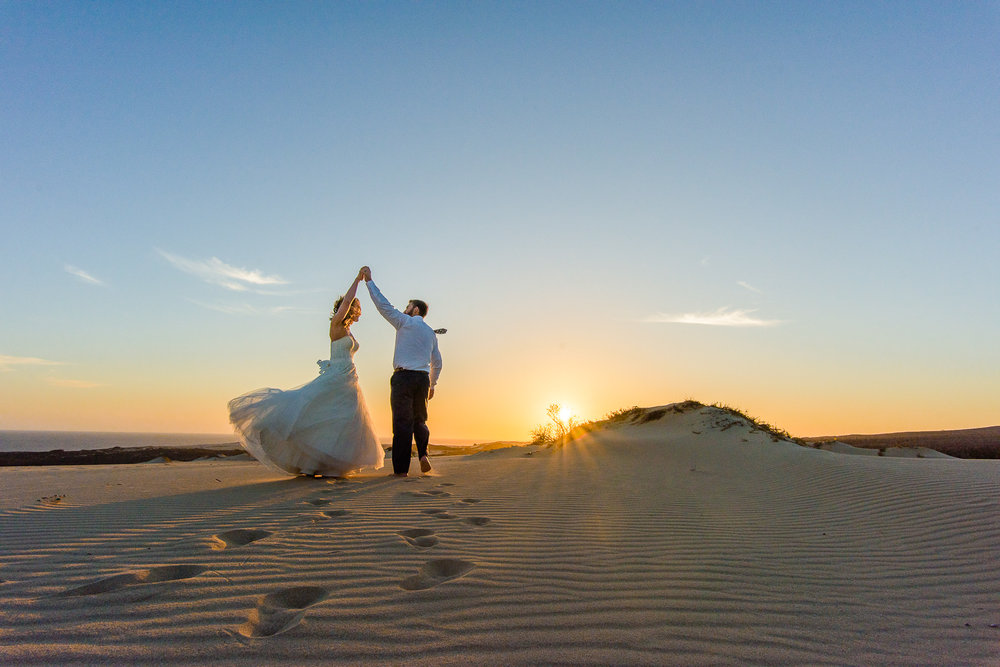 dancing on the dunes bride and groom with a beautifull sky and the dunes during a sunset photo session