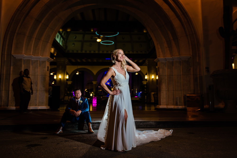 Cabo Beach Wedding. Bride posing at the lobby of Riu Palace Los Cabos, meanwhile groom is waiting for her
