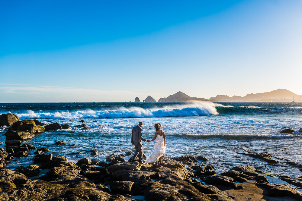 Sunset Monaliss wedding photos. Bride and Groom walking on the rocks with the famous Cabo Arch behind
