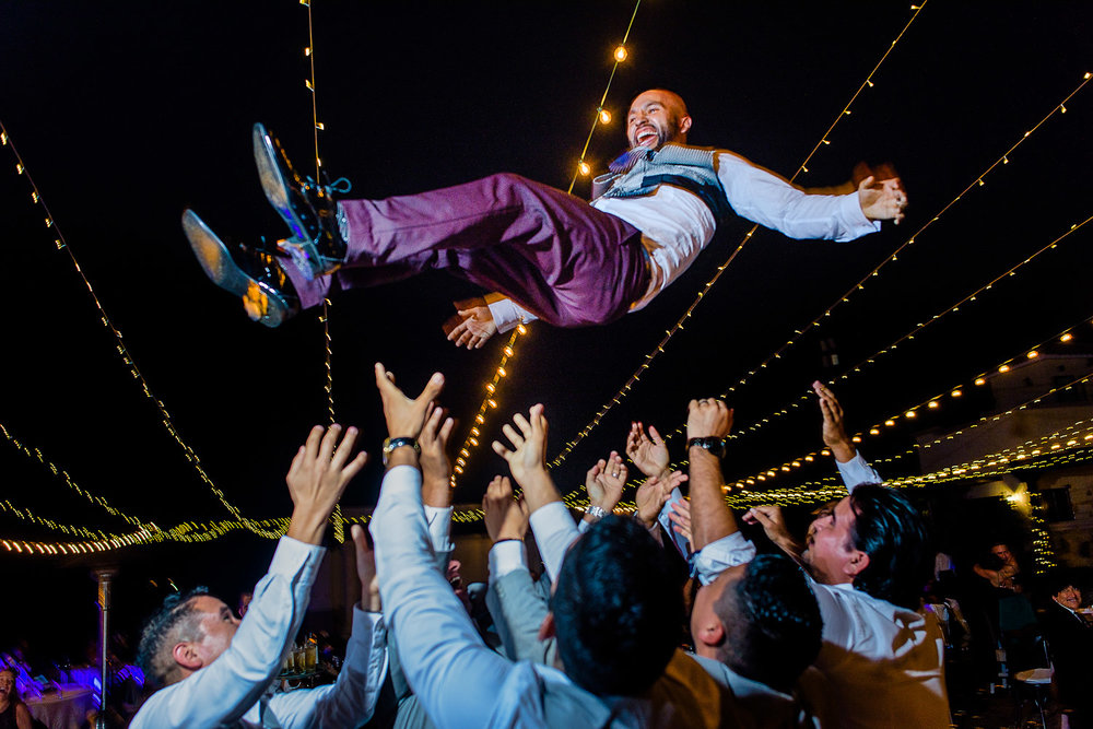 Groom thrown in air by his best friends and groomsmen. Funny moments of a Cabo wedding