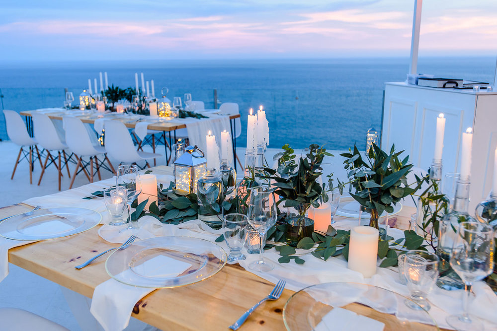 Recepcion boho wedding tables with candles and light and the view of the Pacific Ocean capturedd by professional Cabo wedding photographer GVphotographer. Pedregal Vila Wedding