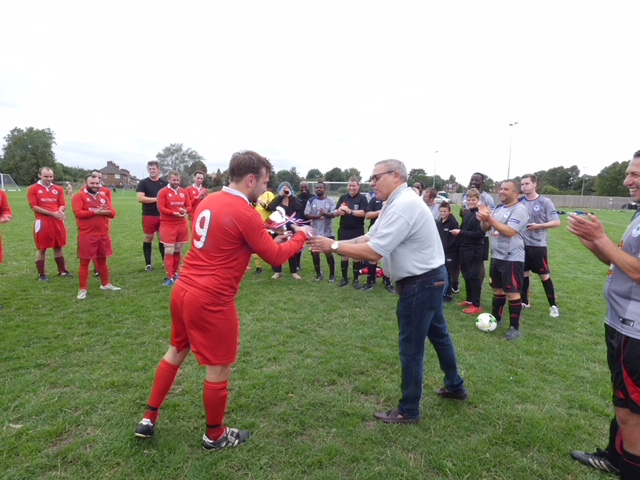 Woolwich Spartans are handed the A & H International Cup by League Chairman Dave Fone