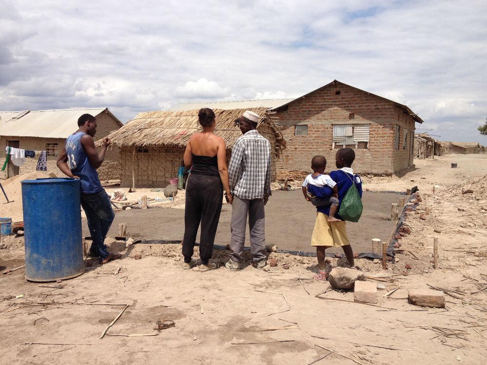 Carmen en 'baba' (de 'grootvader' of verantwoordelijke familieoudste) overschouwen de fundering van het nieuwe huisje die aan het uitharden is. Hierop zal een houten hut gebouwd worden.