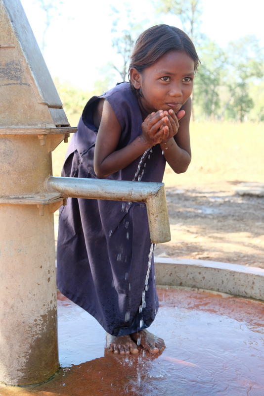 Dhriti drinks water from the new handpump