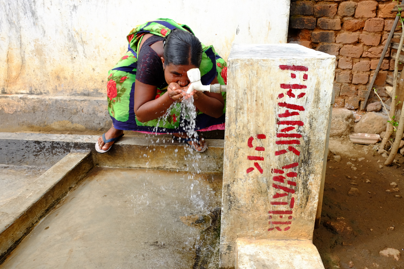 A woman drinks from a frank water tap