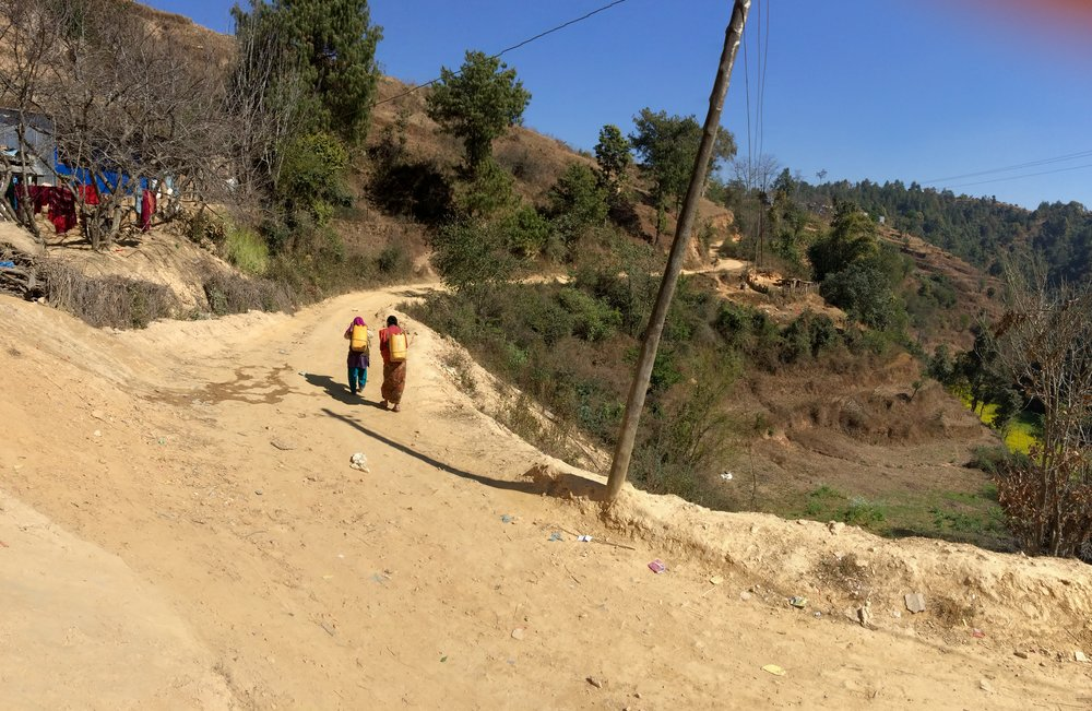 Women carrying water from the bottom of the hill to their homes at the top
