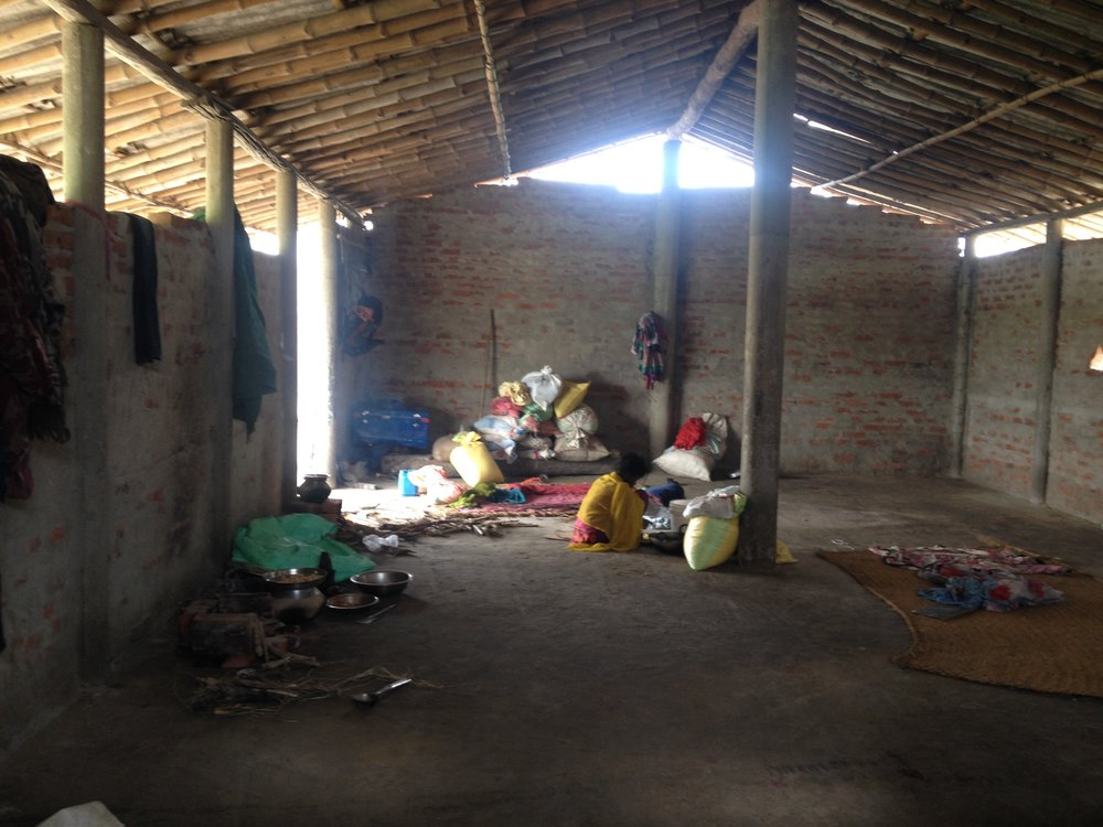 Displaced families lay out blankets to sleep in temporary shelters