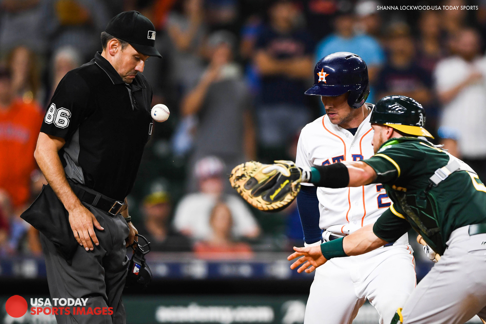 Jul 10, 2018; Houston, TX, USA; The baseball bounces off the chest of umpire David Rackley (86) as Oakland Athletics catcher Jonathan Lucroy (21) tries to tag out Houston Astros third baseman Alex Bregman (2) at home plate during the eleventh inning at Minute Maid Park. Mandatory Credit: Shanna Lockwood-USA TODAY Sports