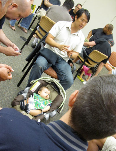 A Veteran Dad (with his baby) answers questions from dads-to-be during the small-group part of a Boot Camp workshop.
