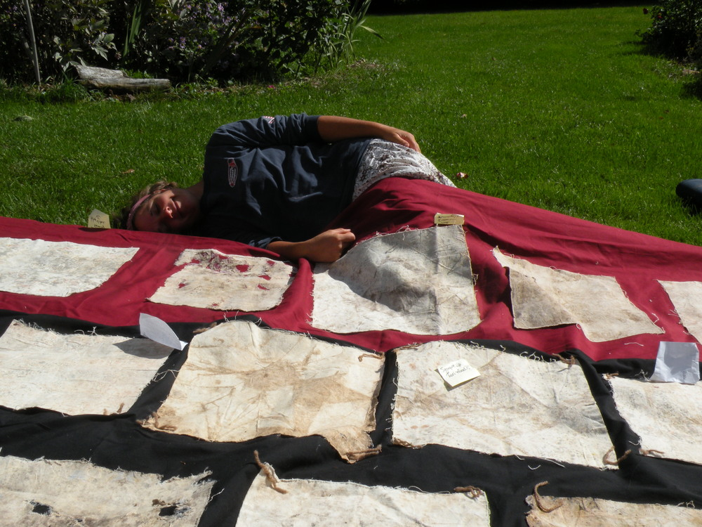 Erin lying down with the quilt before installing for the Farm/Art Dtour. Photo by Rob McClure