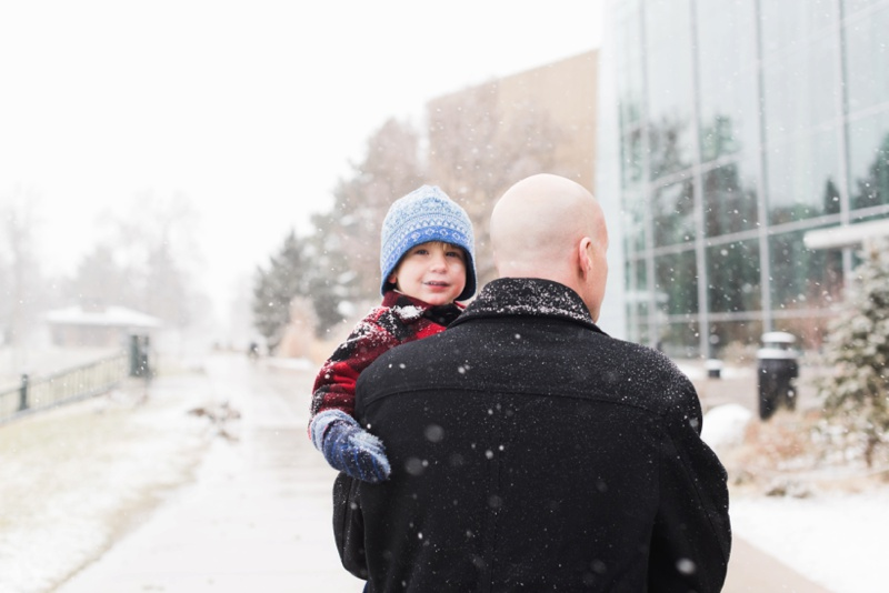 an adorable boy is carried by his father on a snowy afternoon at City Park in Denver, Colorado.  Film photography by Sonja Salzburg of Sonja K Photography.