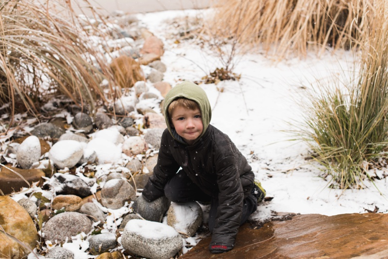 a young boy in a a black jacket with a green hood plays in a dry creek bed on a snowy day at City Park in Denver, Colorado. Film photography by Sonja Salzburg of Sonja K Photography.