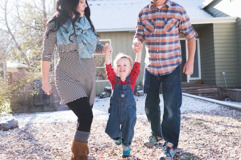 a cute boy in denim overalls plays with his mother and father outside in loveland colorado. Film family portrait by Sonja Salzburg of Sonja K Photography.