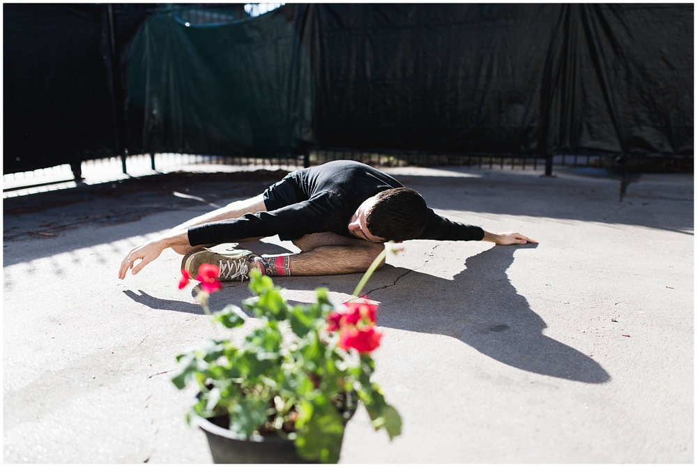 Sonja K Photography portrait of a dancer in the backyard of an LGBTQ house in Denver with gorgeous afternoon light and a red geranium.