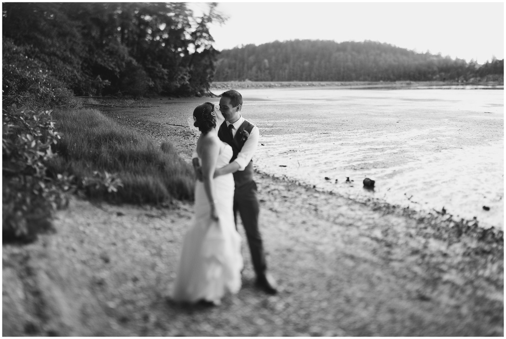 A newly married couple share a quiet moment on Chuckanut Bay, outside Bellingham Washington. Film wedding photography by Sonja Salzburg of Sonja K Photography.