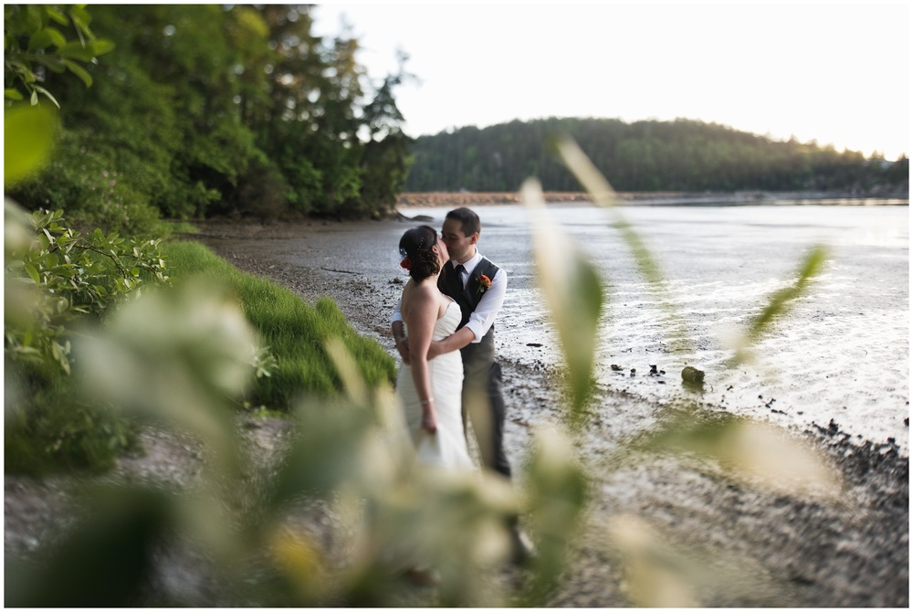 A newly married couple share a private moment on an ocean beach in Chuckanut Bay, Bellingham Washington. Film wedding photography by Sonja Salzburg of Sonja K Photography.