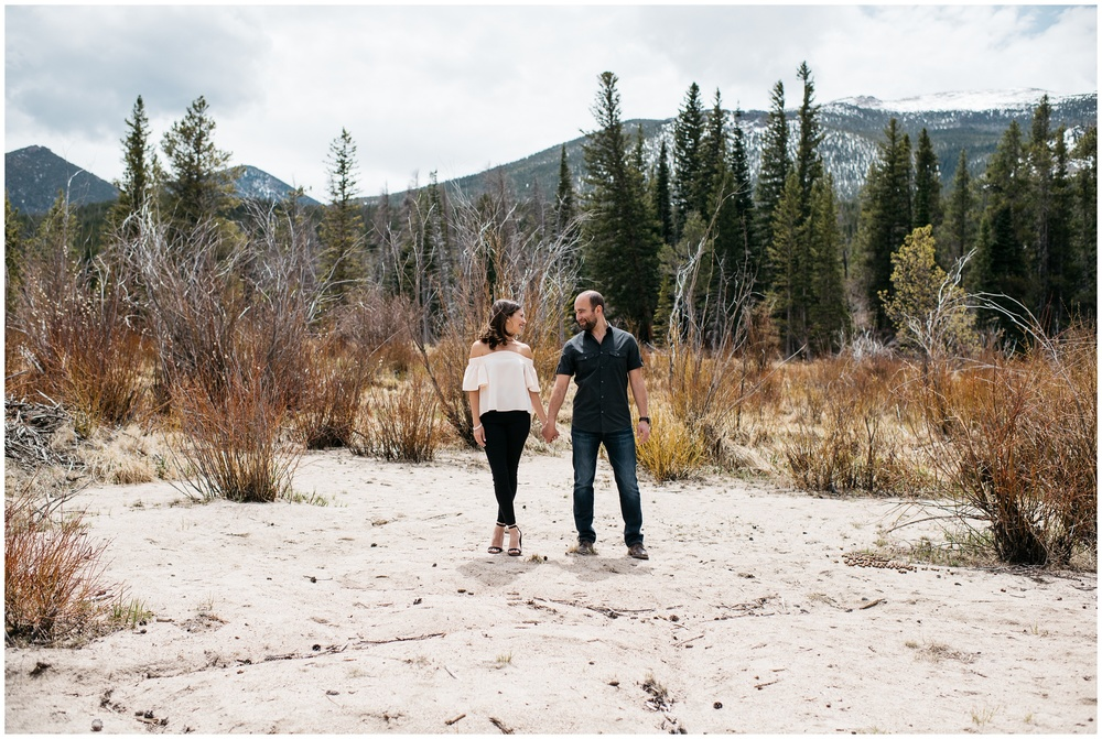 A young, beautiful, engaged couple walk on the beach of Sprague Lake in Rocky Mountain National Park, Colorado. Engagement photography by Sonja Salzburg of Sonja K Photography.