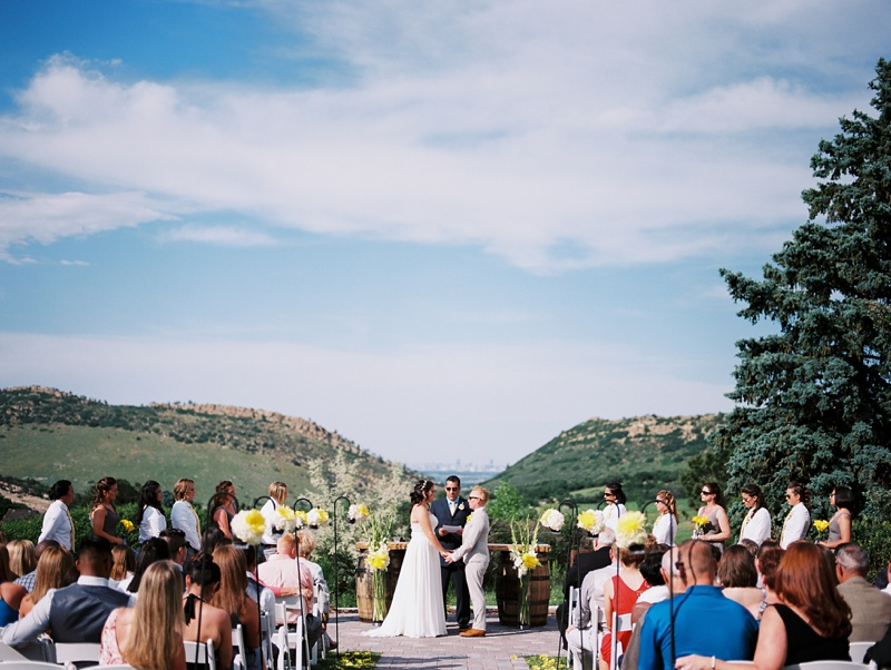 A wedding ceremony at The Manor House in Ken-Caryl Ranch, Colorado with Denver in the distance. Wedding photography by Max Salzburg of Sonja K Photography.