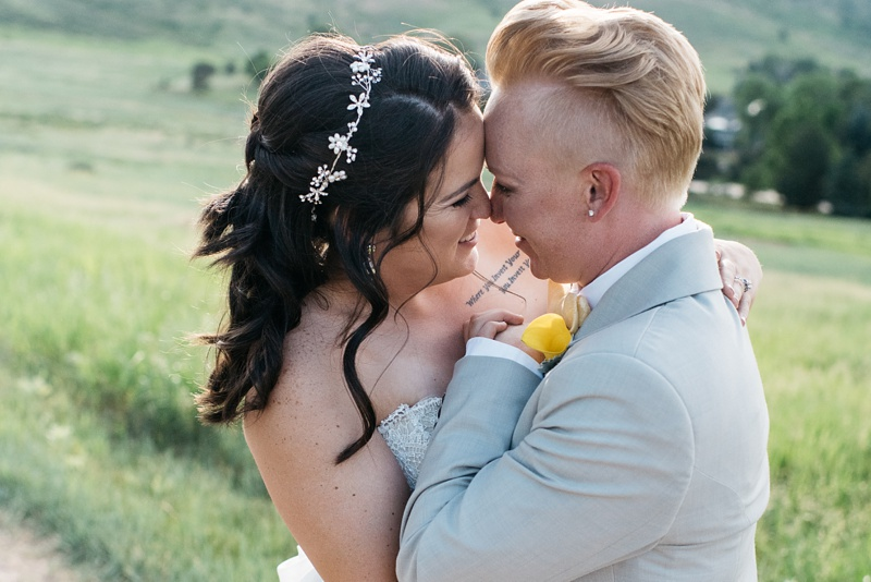 Sweet lesbian couple sharing an intimate moment on their wedding day in the fields behind the Manor House in Colorado.  Photography by Sonja Salzburg of Sonja K Photography