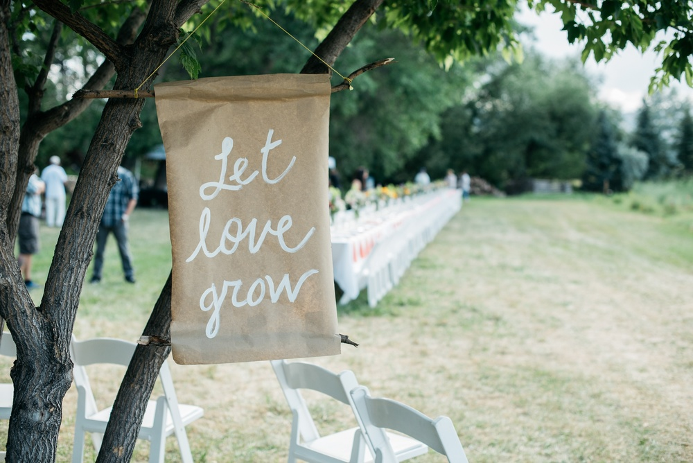 Let love grow sign at the Fortified Collaborations Heart of Summer Farm Dinner at Happy Heart Farm in Fort Collins, Colorado. Event photography by Sonja Salzburg of Sonja K Photography.