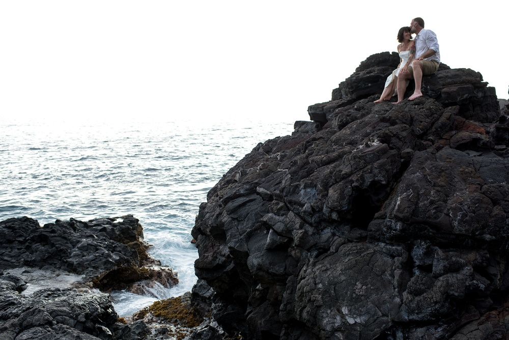 Dan and Maarit on a lava rock overlooking the ocean near Naalehu, Hawaii. Anniversary photography by Sonja Salzburg of Sonja K Photography.