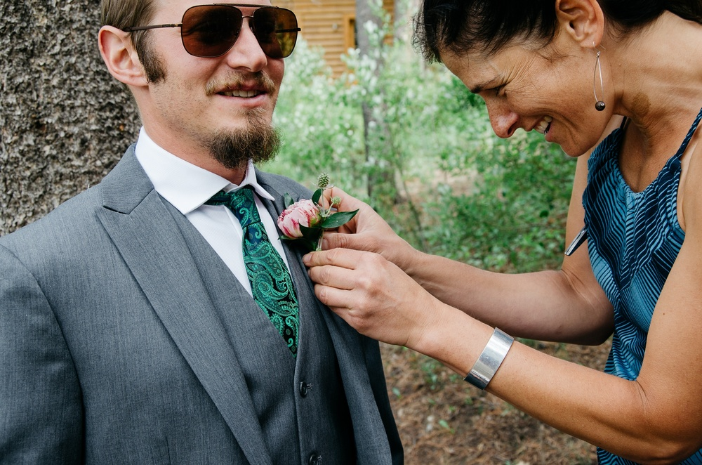 A groom gets his boutonniere pinned on his jacket at Camp Hale near Vail, Colorado. Wedding photography by Max Salzburg of Sonja K Photography.