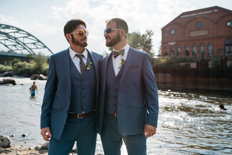 Newly married grooms on the banks of the South Platte River at Confluence Park in Denver, Colorado. Wedding photography by Sonja Salzburg of Sonja K Photography.