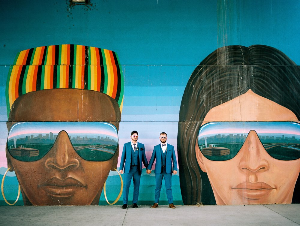 "Karl and Weston by a colorful painted mural called ""Confluent People"" by Emanuel Martinez near Confluence Park in Denver, Colorado. Wedding photography by Sonja Salzburg of Sonja K Photography."