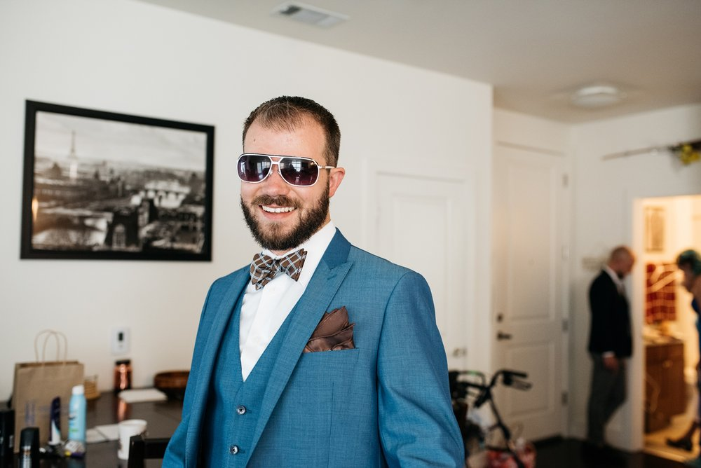 Weston gets ready for his wedding day at Confluence Park in Denver, Colorado. Wedding photography by Sonja Salzburg of Sonja K Photography.