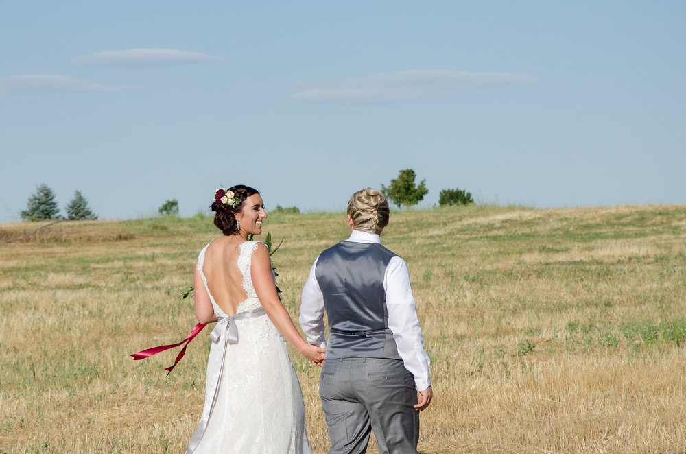 Two brides walk through a field on their wedding day at Windsong Estate in Fort Collins, Colorado. Wedding photography by Sonja Salzburg of Sonja K Photography.