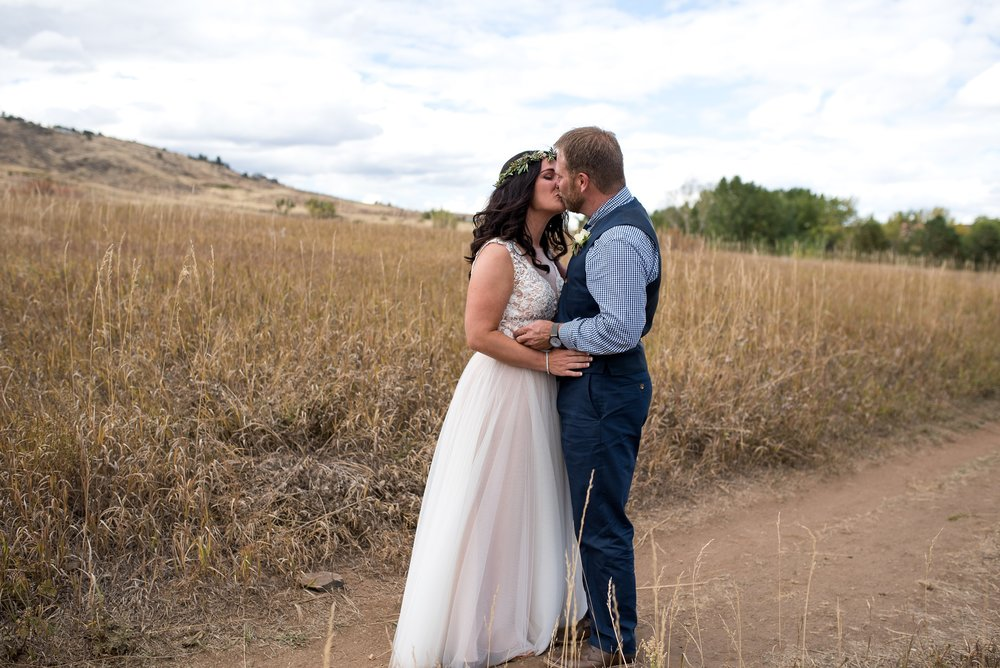 Julie and Chris kiss at their reveal at Lory State Park near Fort Collins, Colorado. Wedding photography by Sonja Salzburg of Sonja K Photography.