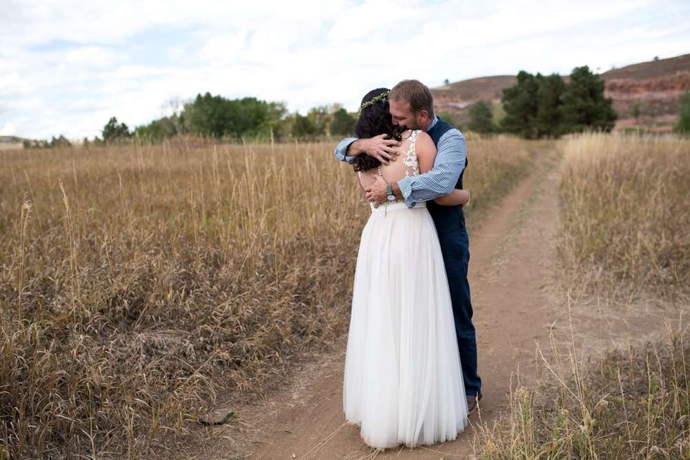 Julie and Chris hug after their reveal at Lory State Park outside of Fort Collins, Colorado. Wedding photography by Sonja Salzburg of Sonja K Photography.