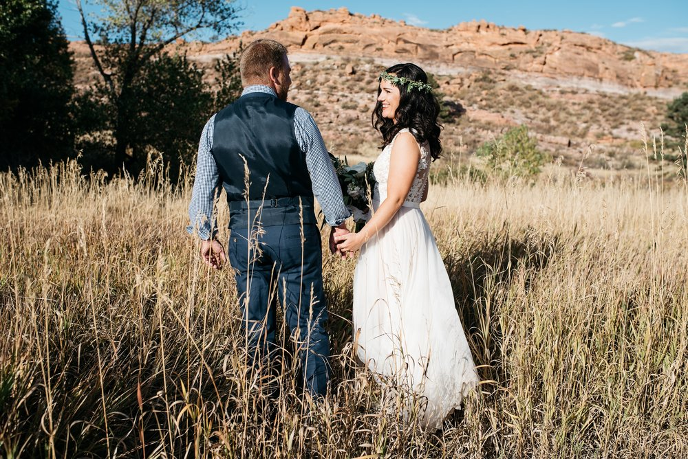 A bride and groom walk though the high grass in Soldier Canyon in Lory State Park outside Fort Collins, Colorado. Wedding photography by Sonja Salzburg of Sonja K Photography.
