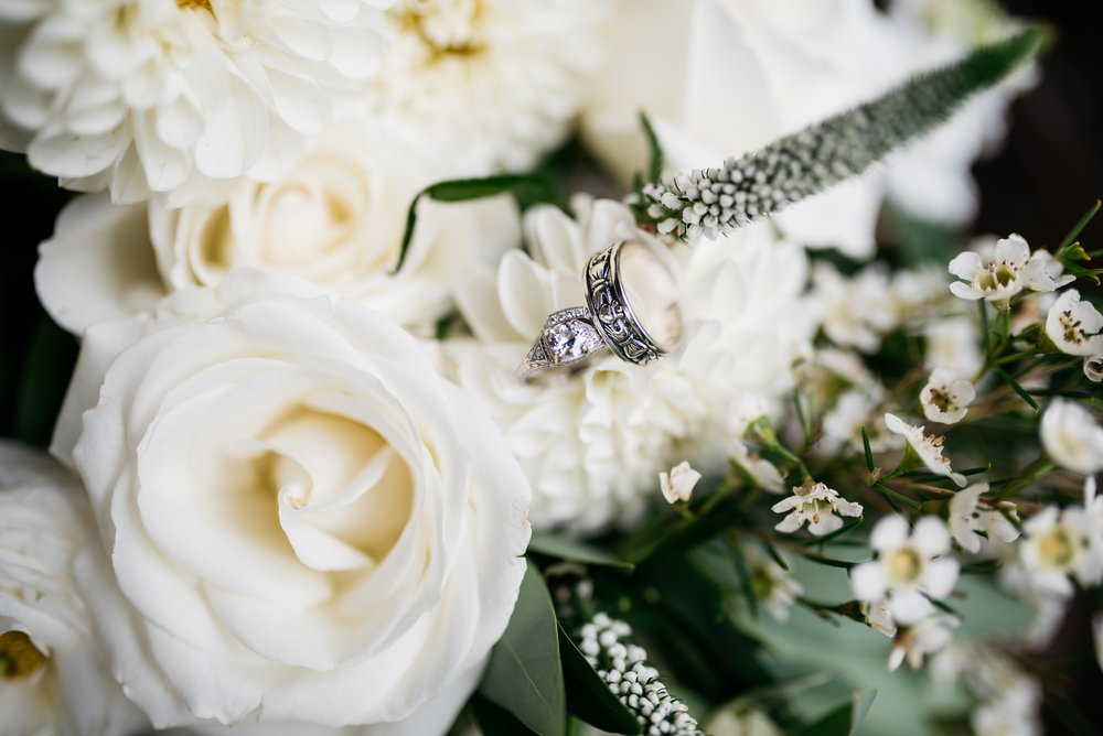 Wedding rings sparkle on bright white roses. Wedding detail photography by Sonja Salzburg of Sonja K Photography.