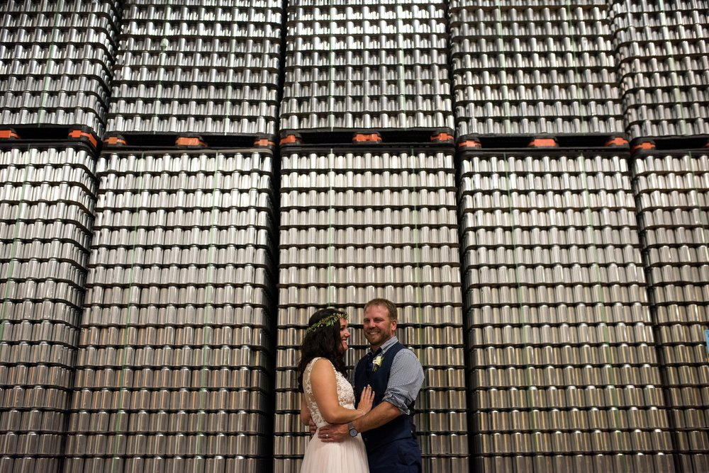 A bride and groom in front of cans at a local brewery in Fort Collins, Colorado. Wedding photography by Sonja Salzburg of Sonja K Photography.