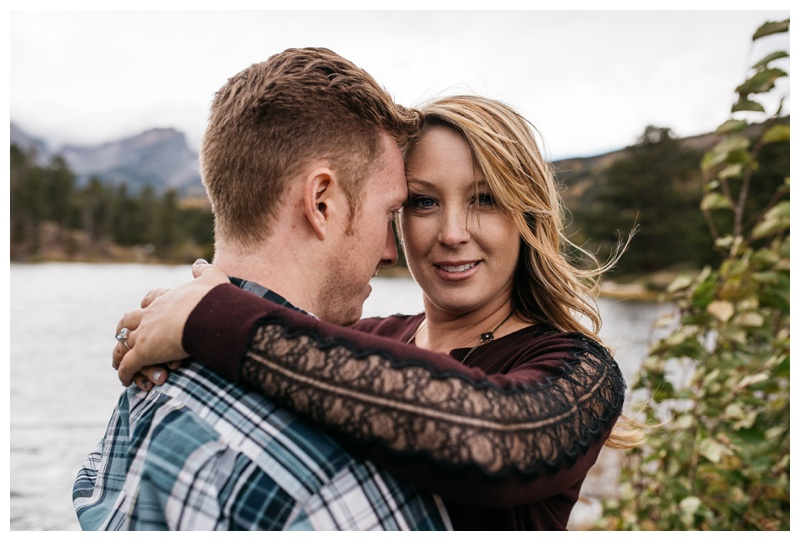 A happy couple at Sprague Lake in Rocky Mountain National Park in Colorado. Engagement photography by Sonja Salzburg of Sonja K Photography.