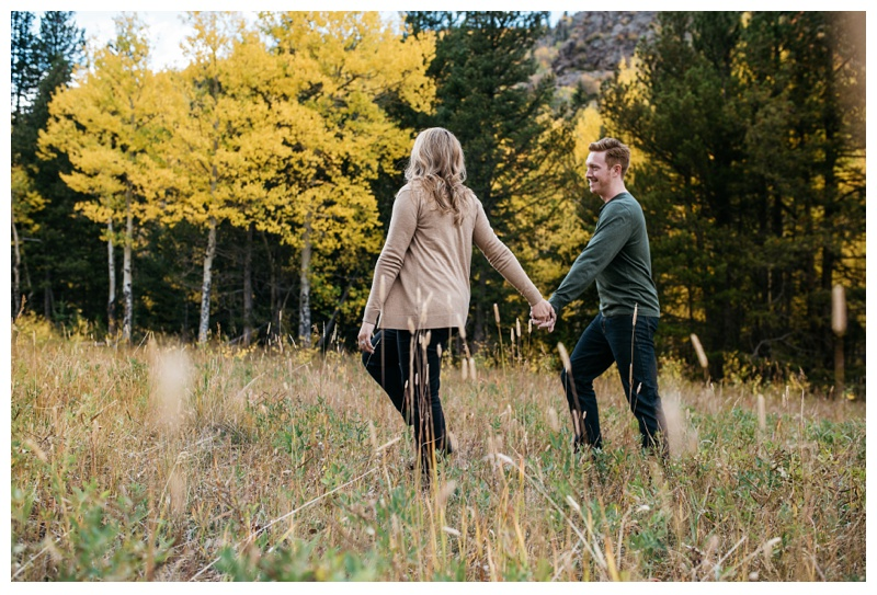 A newly engaged couple walks near golden aspen trees in Rocky Mountain National Park. Engagement photography by Sonja Salzburg of Sonja K Photography.