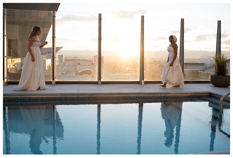 The brides meet at sunset at the pool at Spire Denver. Wedding photography by Sonja Salzburg of Sonja K Photography.