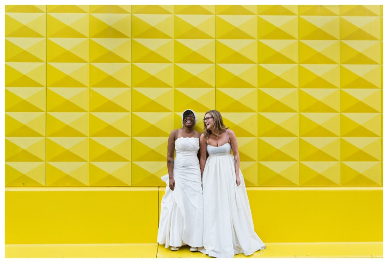 Ali and Kinya laughing at the yellow wall in downtown Denver, Colorado. Wedding photography by Sonja Salzburg of Sonja K Photography.