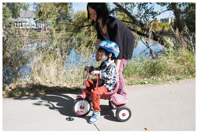 A little boy on his tricycle with his mother on the Spring Creek Trail in Fort Collins, Colorado. Family portrait photography by Sonja Salzburg of Sonja K Photography.