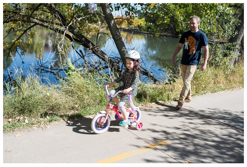 A little girl on her bike with her father on the Spring Creek Trail in Fort Collins, Colorado. Family portrait photography by Sonja Salzburg of Sonja K Photography.
