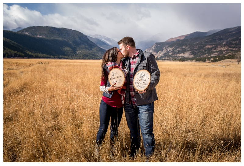 An engaged couple with cute signs at Moraine Park in Rocky Mountain National Park in Colorado. Engagement photography by Sonja Salzburg of Sonja K Photography.