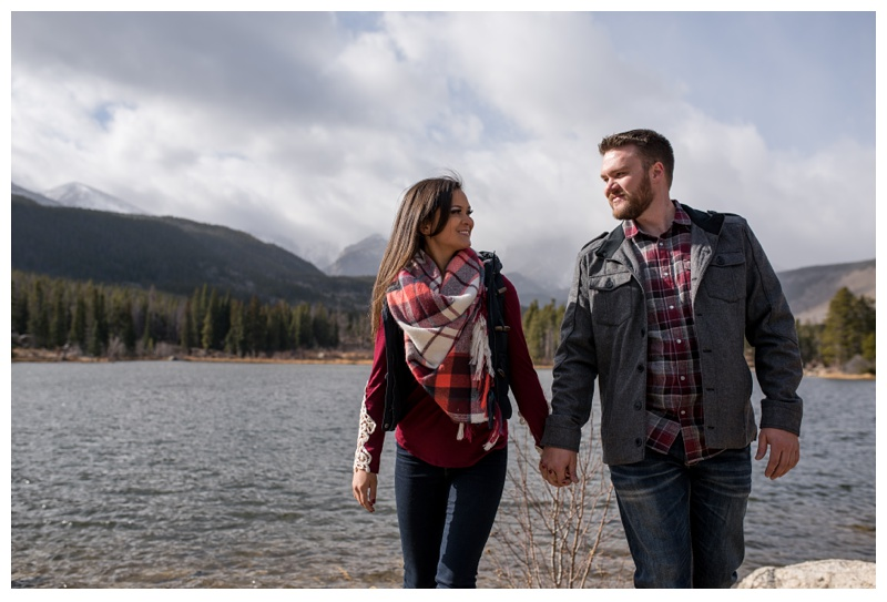 An engaged couple at Sprague Lake in Rocky Mountain National Park in Colorado. Engagement photography by Sonja Salzburg of Sonja K Photography.