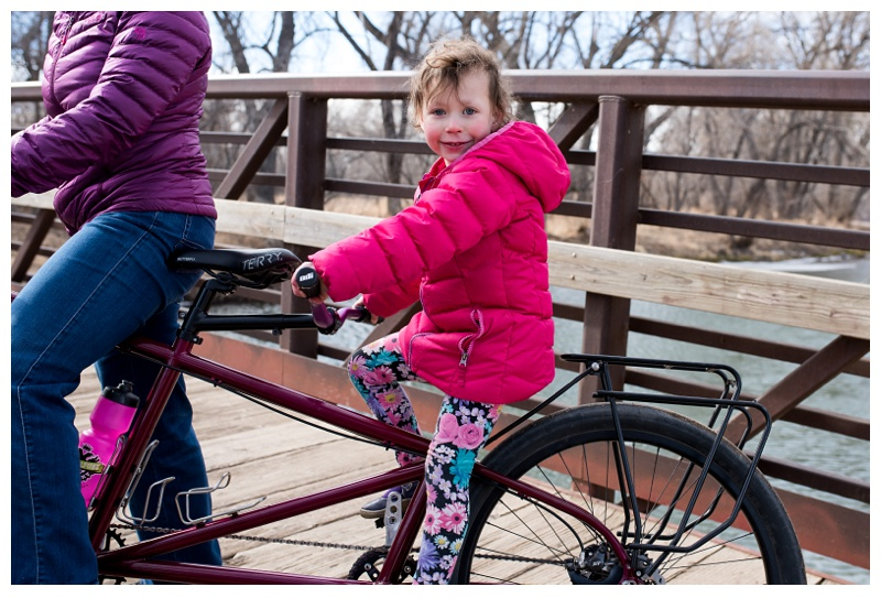A happy little girl on her tandem bike from Kelpie Cycles at Lee Martinez Park in Fort Collins, Colorado. Family portraits by Sonja Salzburg of Sonja K Photography.