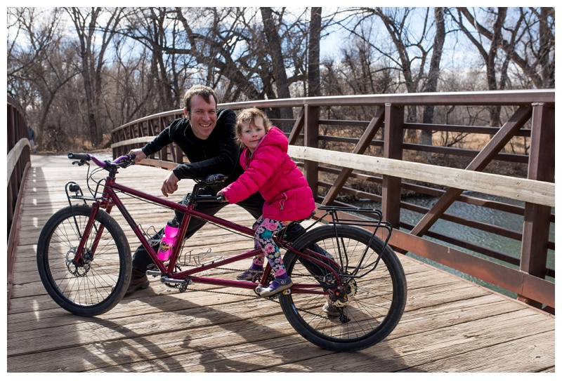 A father and his daughter on a Kelpie Cycles tandem bike in Lee Martinez Park Fort Collins, Colorado. Family portrait photography by Sonja Salzburg of Sonja K Photography.