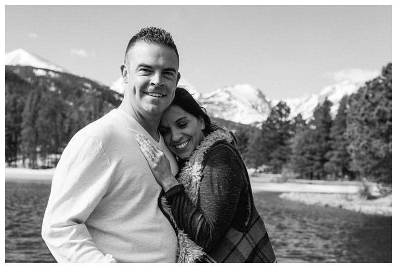 A black and white photo of a happily engaged couple at Sprague Lake in Rocky Mountain National Park in Colorado. Engagement photography by Sonja Salzburg of Sonja K Photography.