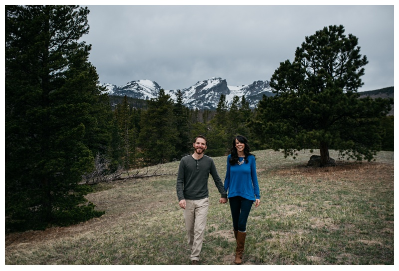 Christine and Jameson walk though a meadow in Rocky Mountain National Park. Wedding engagement photography by Sonja Salzburg of Sonja K Photography.